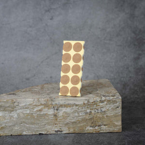 A sheet of tan acupressure adhesives propped up on a slab of marble.