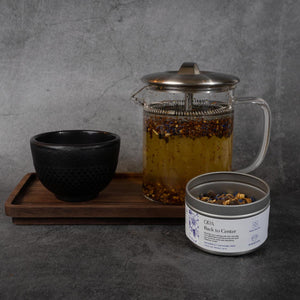 On the right, the same tin of tea as in the previous photos, with some of the loose-leaf visible. Behind the tin is a black ceramic cup and a clear tea pot, which has tea and loose-leaf tea leaves floating in it.