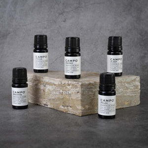 The full CAMPO Essential Oil Blend line. From left to right: Breathe, Focus, Energy, Relax, Sleep. All blends are in matching small black bottles.