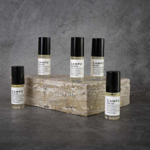 The full CAMPO Essential Oil Roll-on line. From left to right: Focus, Immune, Energy, Sleep, Relax. All Roll-ons are in matching glass bottles.