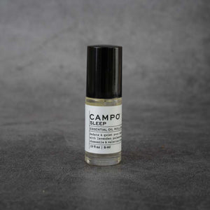 "A small clear glass bottle with a white label. The label reads ""CAMPO Sleep Essential Oil Roll-on, Sedate & quiet your mind with lavender, palmarose, chamomile & valerian root, .17 fl oz, 5 ml"". The bottle has a black twist-off lid."