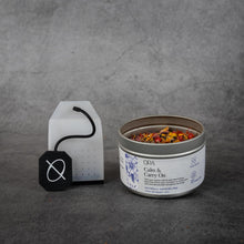 "Load image into Gallery viewer, On the left, clear silicone tea bag with a black silicone string printed with the ORA logo. On the right, a small cylinder shaped metal tin of tea reading ""ORA Calm & Carry On"". The tin does not have a lid and some of the loose-leaf tea is visible."