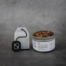 "Load image into Gallery viewer, On the left, a clear silicone tea bag with a black silicone string printed with the ORA logo. On the right, a small cylinder shaped metal tin of tea reading ""ORA Find Your Focus"". The tin does not have a lid and some of the loose-leaf tea is visible."