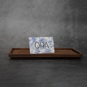 "An ORA gift card. The gift card is white with a navy floral print and the word ""ORA"" in black lettering."