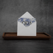 "Load image into Gallery viewer, An ORA gift card peeking out of a white envelope. The gift card has a navy floral pattern on it and the word ""ORA"" in black lettering."