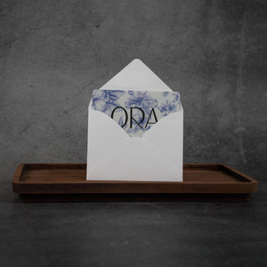 "An ORA gift card peeking out of a white envelope. The gift card has a navy floral pattern on it and the word ""ORA"" in black lettering."