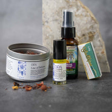 Load image into Gallery viewer, From left to right: a metal tin of ORA Line of Defense loose-leaf tea with no lid, ORA by CAMPO essential oil roll-on, Myco Shield Immune Support spray, and a box of Yin Chiao herbal supplements.