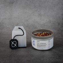 "Load image into Gallery viewer, On the left, a clear silicone tea bag with a black silicone string printed with the ORA logo. On the right, a small cylinder shaped metal tin of tea reading ""ORA Line of Defense"". The tin does not have a lid and some of the loose-leaf tea is visible."