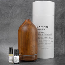 "Load image into Gallery viewer, The same wooden diffuser as in the previous picture, with a set of ORA by Campo essential oils next to it. Behind the diffuser is the packaging for the diffuser, a tall white cylinder reading ""Campo Diffuser, Ultrasonic Essential Oil Diffuser""."