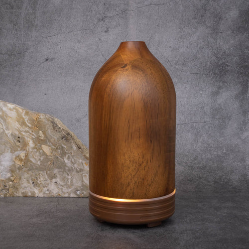 A cone-shaped dark wooden essential oil diffuser. There is band of light around the bottom indicating it has been turned on.
