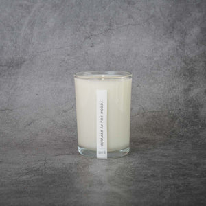 "A white candle in a clear glass jar. A small rectangular label on the candle reads ""Sera, Summer in the Woods"""