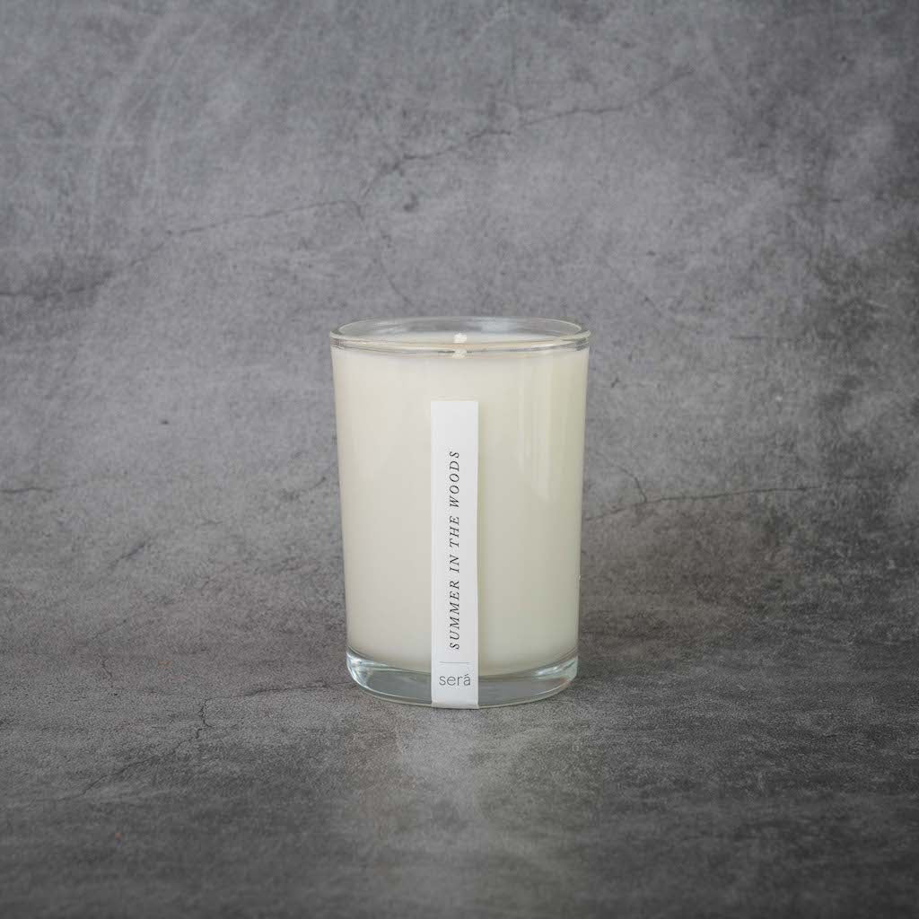 A white candle in a clear glass jar. A small rectangular label on the candle reads