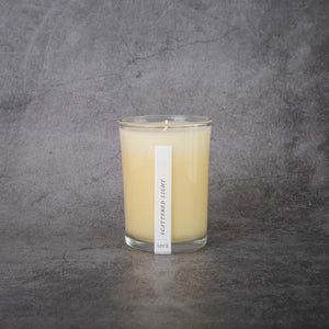 "A cream-colored candle in a clear glass jar. The candle has a small rectangular label that reads ""Sera, Scattered Light""."