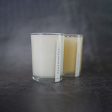 Load image into Gallery viewer, In the foreground of the picture is the Sera Summer in the Woods candle. Behind it, slightly out of focus, is the Sera Scattered Lights candle.