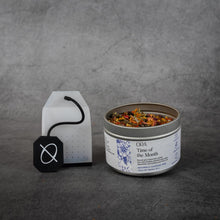 "Load image into Gallery viewer, On the left, a clear silicone tea bag with a black silicone string printed with the ORA logo. On the right, a small cylinder shaped metal tin of tea reading ""ORA Time of the Month"". The tin does not have a lid and some of the loose-leaf tea is visible."