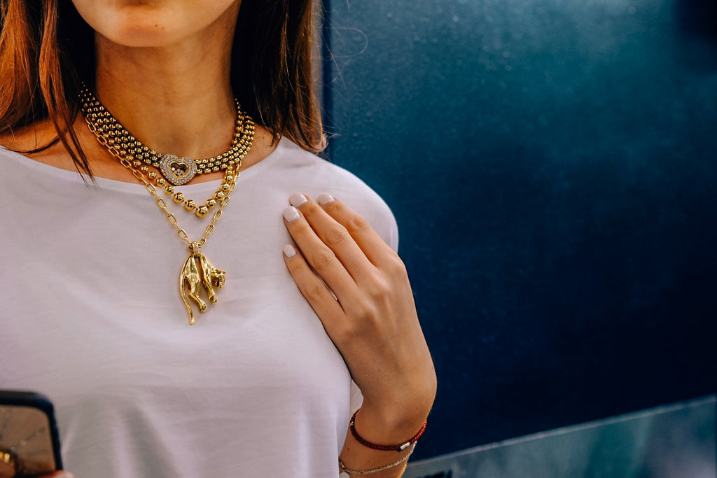 Cartier and Chopard yellow gold necklaces on a neck.