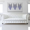 Trio Of Devils White & Blue Canvas Art shown on a wall in a white room with sofa