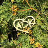 ADK in a heart natural wood ornament hanging on a tree branch.