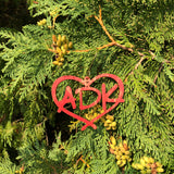 ADK in a heart red wood ornament hanging on a tree branch.