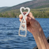 Stainless bottle opener with a heart on top and the letter L above G, opener tab on the bottom.
