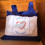 Love is in New York blue text around  the map of the state of New York with a red heart.  It is a blue reusable tote that holds up to 25#.