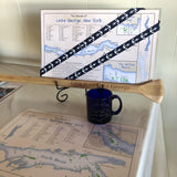 Laminated map of the Islands of Lake George including some fun facts. Two-sided; white background, blue lake and green islands..  Cobalt Blue Love is on Lake George coffee mug.