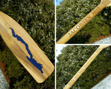 5' wooden oar with the Silhouette of Lake George cut out on the blade and painted lake blue; the Personalizaton Lasered on the oar handle.