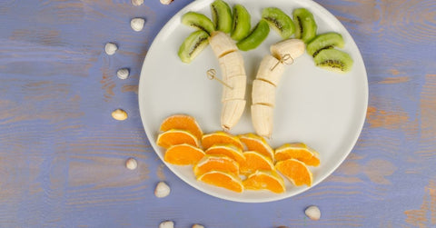 Orange, banana and kiwi palm tree food scene