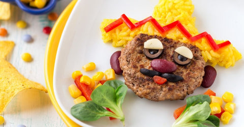 Beef burger, potato and vegetable Mexican face and sombrero scene