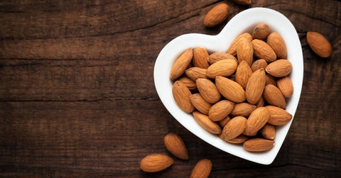 A heart shaped dish of raw almonds