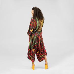 Back view of red multi print bomber jacket with balloon sleeves and pockets as seen on model wearing jumpsuit