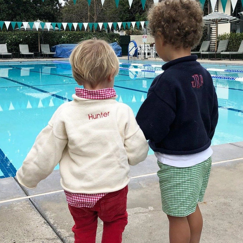 Two boys wearing rollneck sweaters with monogram and personalized with name