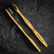 Load image into Gallery viewer, Two Natural Bamboo Toothbrushes, with charcoal bristles showing, on a black stone background.