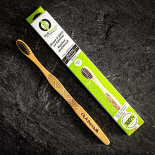 Load image into Gallery viewer, Ola Bamboo Toothbrush, next to green toothbrush box, on a black stone background.
