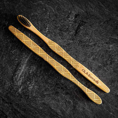 Two natural bamboo toothbrushes, with black bristles on a black stone background.