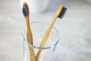Two biodegradable, bamboo toothbrushes, with charcoal bristles in a clear glass on a white counter.