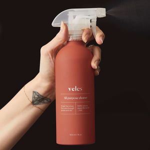 Coral colored, aluminum bottle of Veles zero waste All Purpose Cleaner, spraying into a black background.