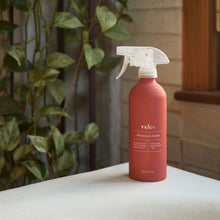 Load image into Gallery viewer, A coral colored aluminum bottle of Veles eco-sustainable all purpose cleaner, on a table with plant in background.