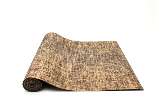 Salvos, Light tan yoga mat made of hemp and jute fibers, partially rolled up on white background.