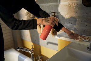 A person spraying Veles, zero waste, all purpose cleaner onto a counter in a bathroom.