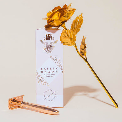 Eco Roots, Rose Gold Safety Razor, with white packaging and a golden rose laying against the packaging.