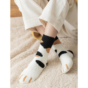 front view of a model wearing the black and orange dot paw socks