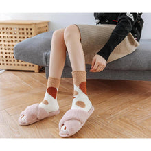 Load image into Gallery viewer, A model wearing the brown dot paw socks with pink home slippers