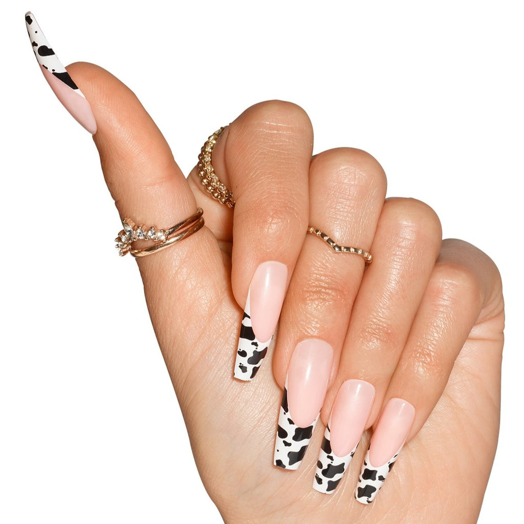 Hand wearing Big Moood nails, natural french with cow print on tip, in coffin shape ultra long length