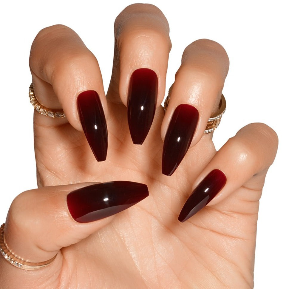 Claw hand wearing Tres She Cherry Cola dark red jelly nails, ballerina shape long length
