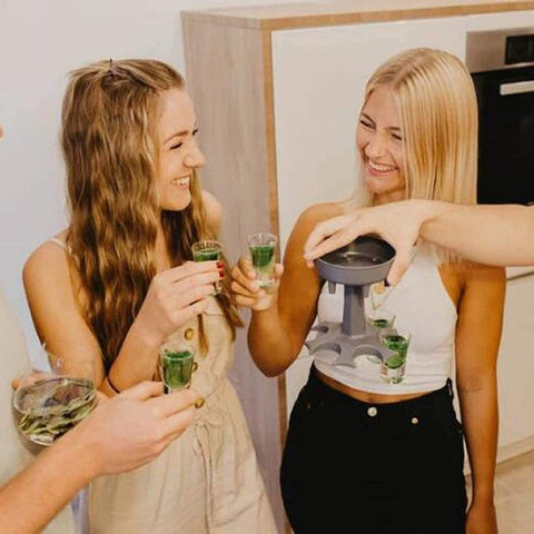 Two women drinking from a shot glass at a party