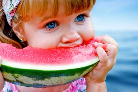 girl eating watermelon on the boat