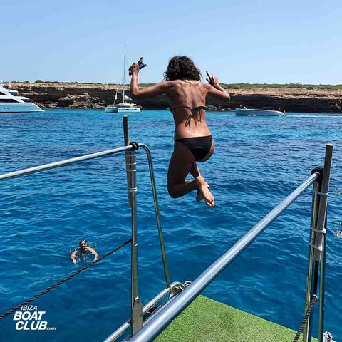 girl jumping from the boat in ibiza with jump board