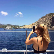 girl taking picture of a yacht in ibiza