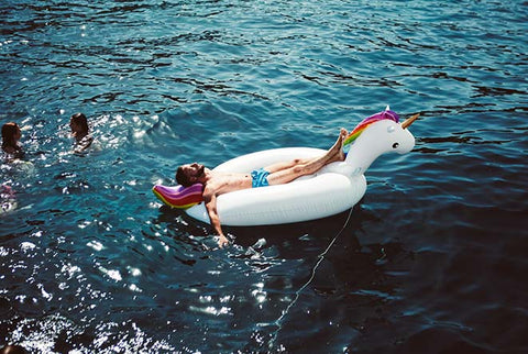 man relaxing on water toy unicorn in the sea